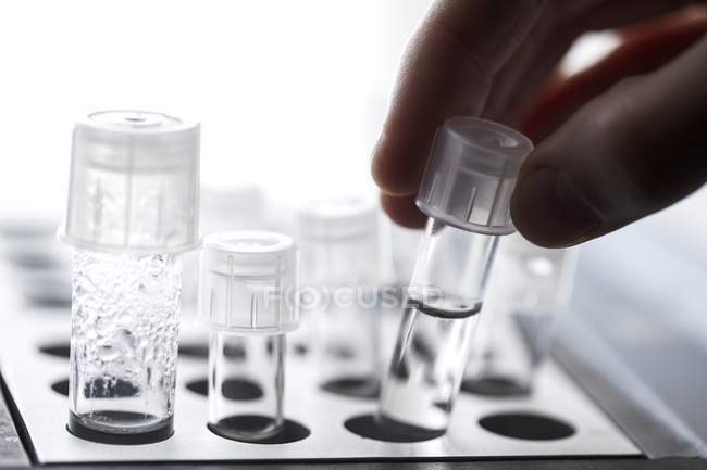 Close-up of scientist taking tubes in in vitro fertilisation lab. — Stock Photo