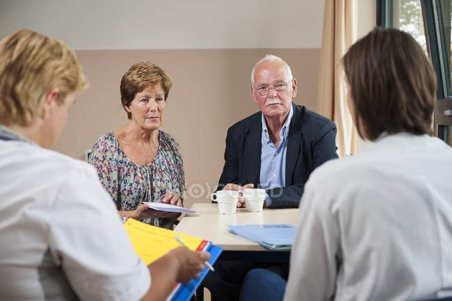 Female doctors having meeting with senior patients. — Stock Photo