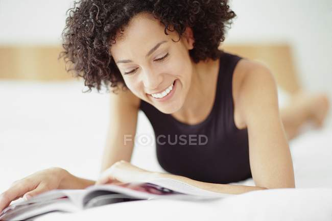 Mid adult mixed race woman reading magazine on bed. — Stock Photo