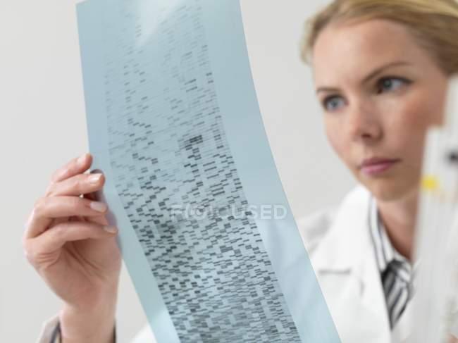 Female scientist examining DNA autoradiogram. — Stock Photo