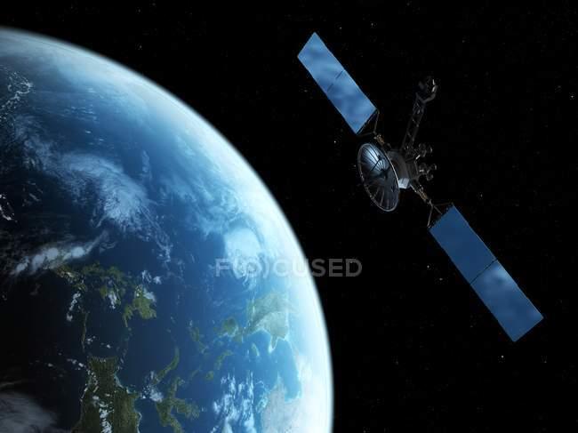Спутник на орбите Земли — стоковое фото