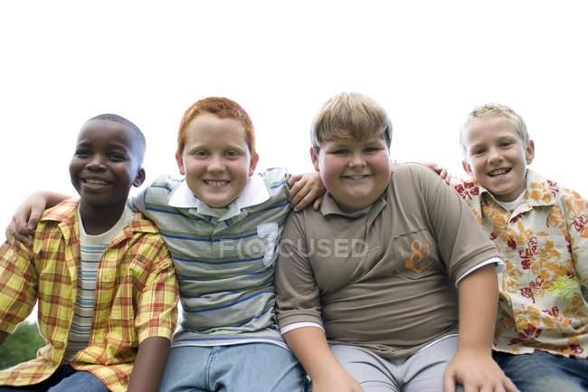 Группа мальчиков, сидящих бок о бок на улице . — стоковое фото