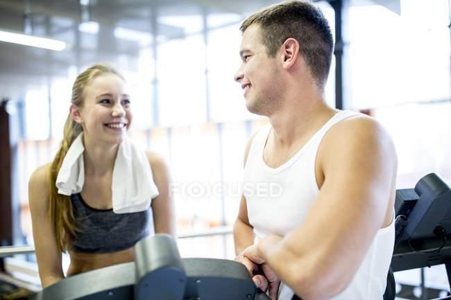 Junger Mann im Gespräch mit Frau am Heimtrainer im Fitness-Studio — Stockfoto