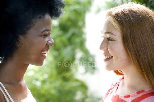 Due adolescenti che comunicano a vicenda all'aperto. — Foto stock