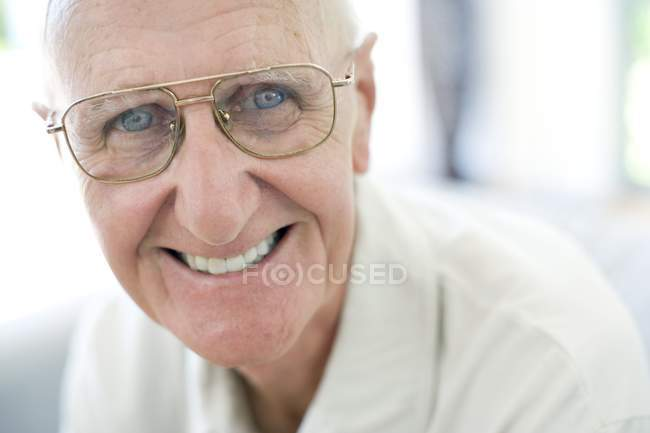 Portrait of happy senior man in classic eyeglasses looking in camera — Stock Photo