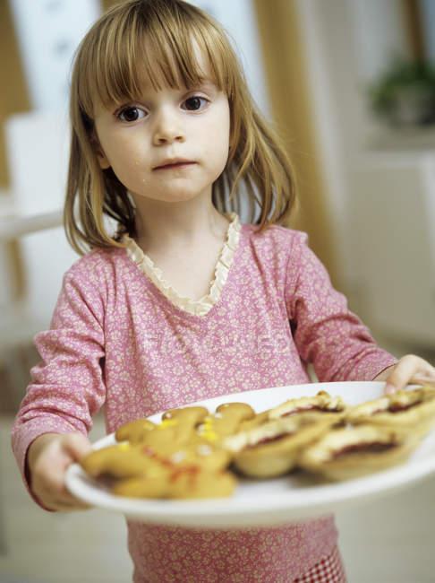 Garota de pré-escola, segurando o prato de biscoitos caseiros e tortas de geleia. — Fotografia de Stock