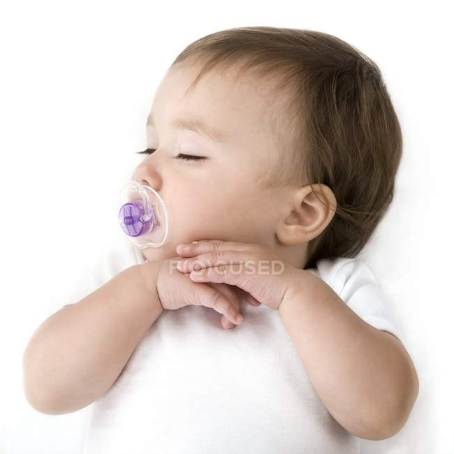 Sleeping baby girl with purple pacifier. — Stock Photo