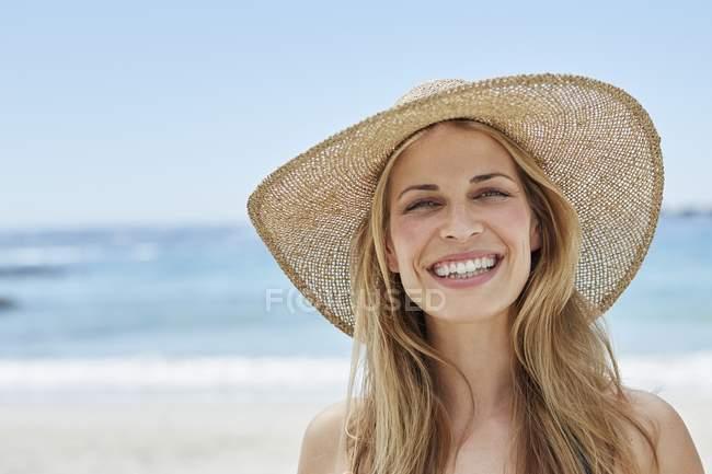 Portrait of woman wearing a sunhat on beach. — Stock Photo