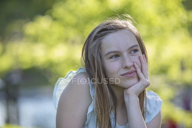 Portrait of smiling teen girl with hand on chin in park. — Stock Photo