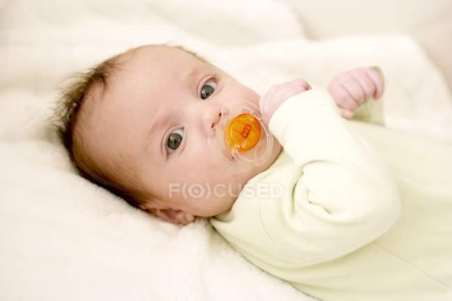 Дитина дівчина смоктати манекен на ліжку. — стокове фото
