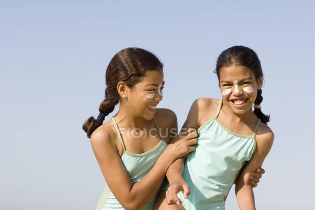 Soeurs avec crème solaire sur les visages jouer combats sur la plage . — Photo de stock