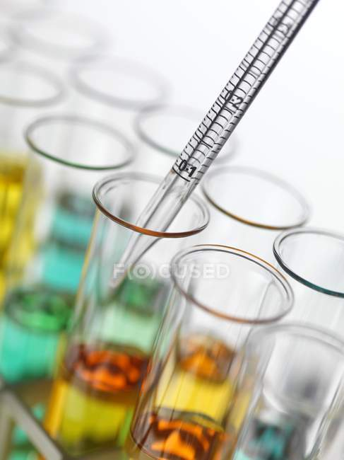 Close-up of pipetting colorful liquids into test tubes. — Stock Photo