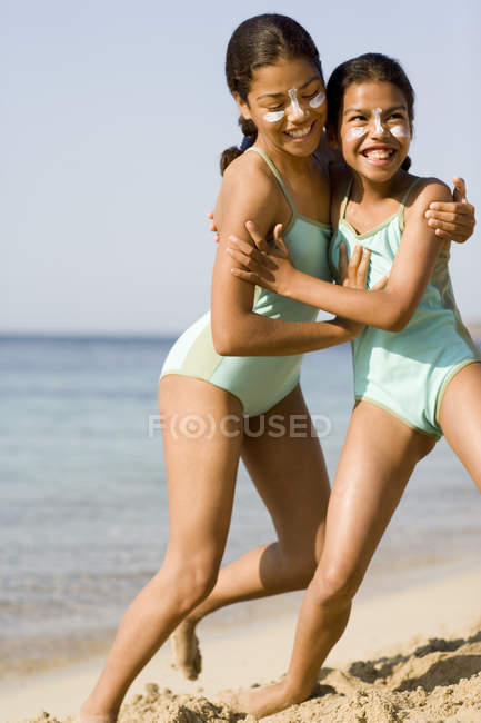 Sisters with sun cream on faces play fighting on beach. — Stock Photo