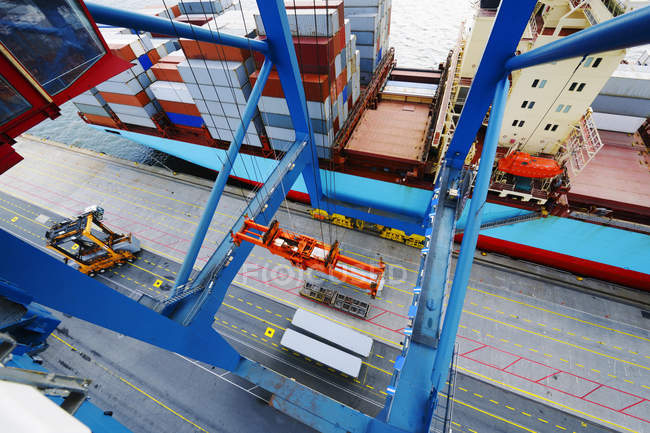 Shipping containers and crane in port, high angle view. — Stock Photo