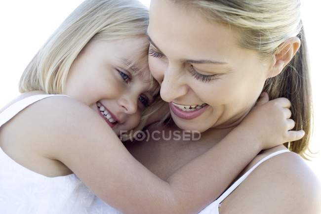 Mother and daughter cuddling and smiling outdoors. — Stock Photo