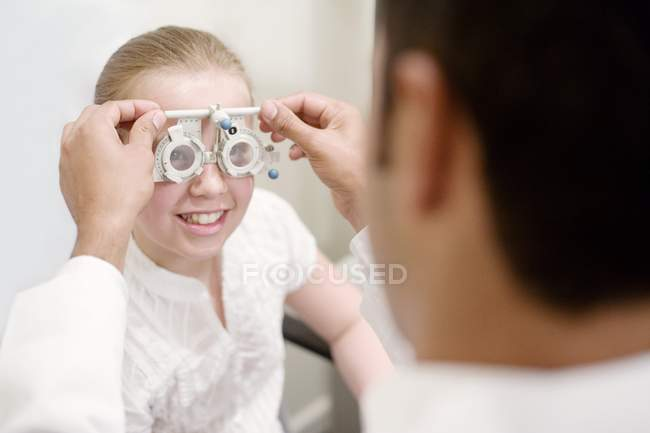 Optician adjusting trial frame for eye examination preteen girl. — Stock Photo