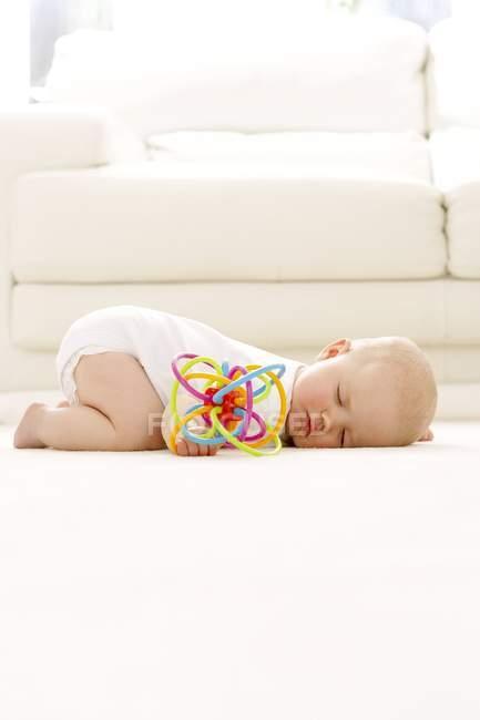 Baby girl sleeping on floor with toy in hand. — Stock Photo
