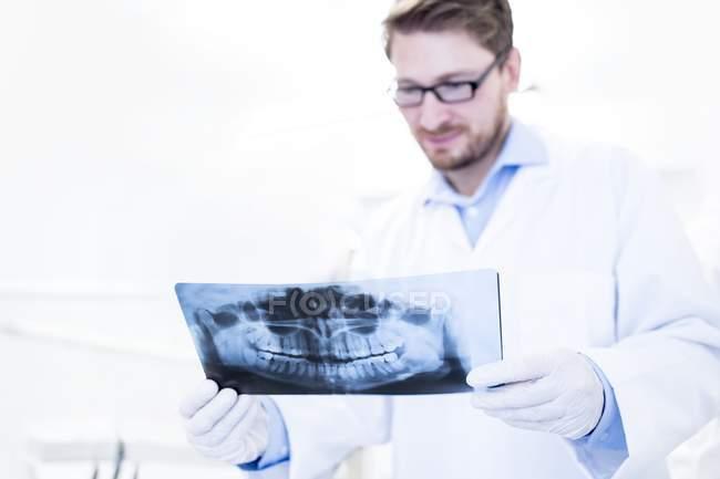 Dentista olhando para a imagem de raio-x — Fotografia de Stock