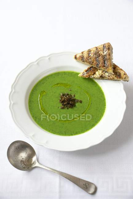 Healthy meal of chilled pea and spinach soup with grilled anchovy toast. — Stock Photo