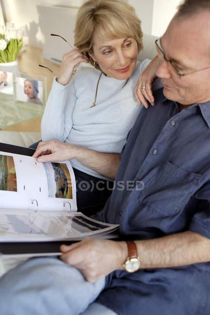 Esposa que se inclina en el hombro de marido mirando el álbum de fotos. - foto de stock