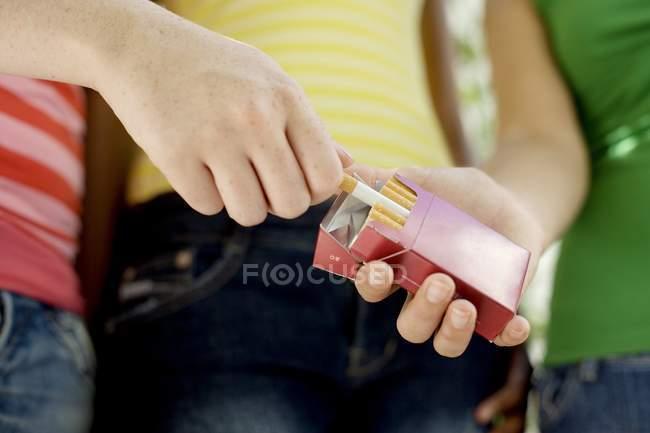 Cigarette prise adolescente du paquet amis — Photo de stock