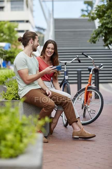 Coppia seduta sulla parete stradale con bici e utilizzando smartphone . — Foto stock