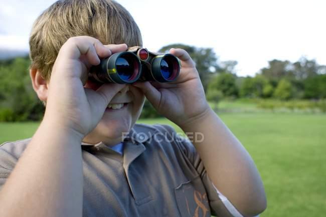 Ожиріння хлопчик, використовуючи бінокль на відкритому повітрі. — стокове фото