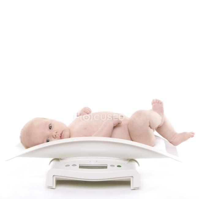 Bambino che si trova sulla scala del peso. — Foto stock