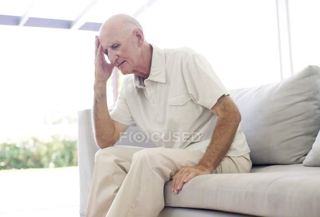 Retrato del hombre mayor sentado en el sofá con la mano en la frente . - foto de stock