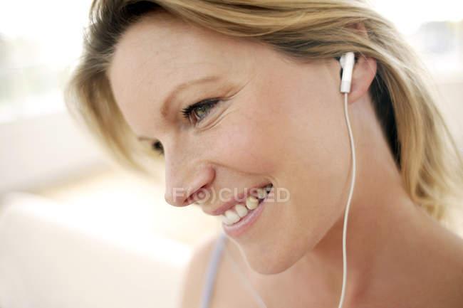 Woman listening to music through earphones. — Stock Photo