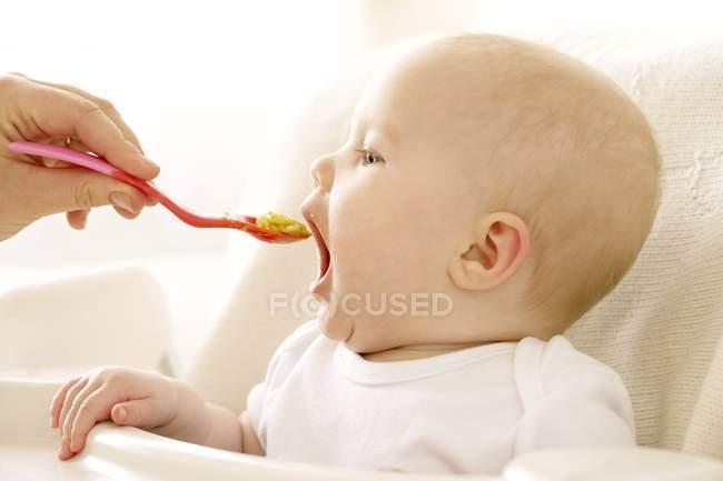 Малышка ест с ложки в стульчике . — стоковое фото