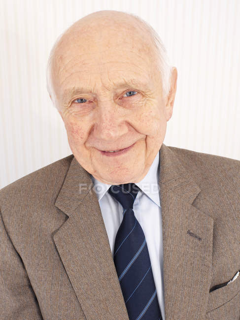 Cheerful senior man in full suit looking in camera, portrait. — Stock Photo