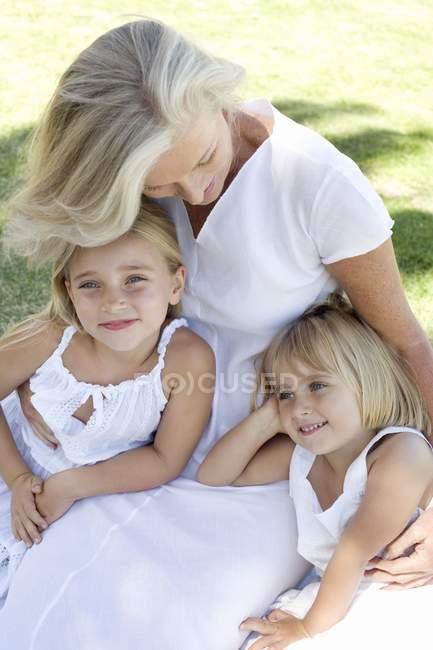 Grandmother cuddling granddaughters in garden. — Stock Photo