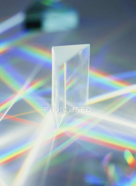 White light passing through triangular prism and producing spectrum. — Stock Photo