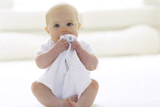 Девочка, жуя одеяло на этаже. — стоковое фото