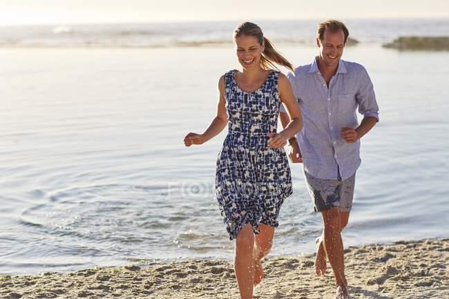 Couple courant sur la plage et souriant . — Photo de stock