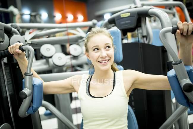 Frau mit Butterfly-Maschine im Fitness-Studio — Stockfoto