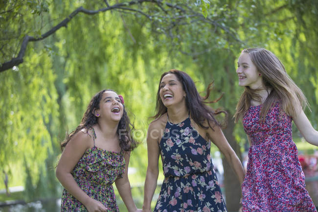Latin mother laughing with teen girls in park. — Stock Photo