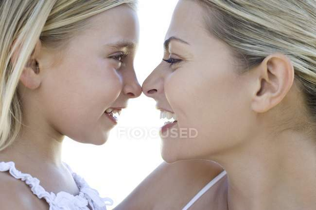 Mother and daughter rubbing noses outdoors. — Stock Photo