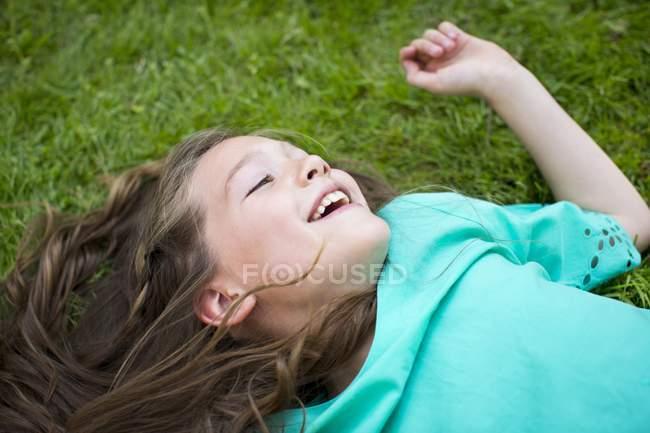Jeune fille couchée sur l'herbe et souriant . — Photo de stock