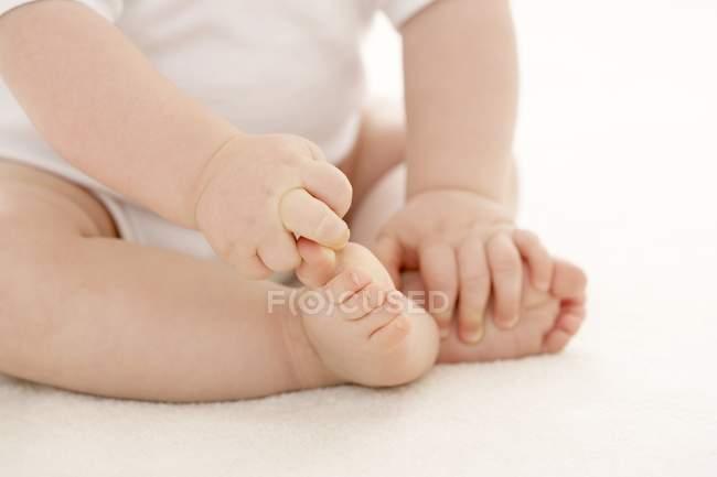 Младенец размахивает большим пальцем ноги, сидя на полу . — стоковое фото