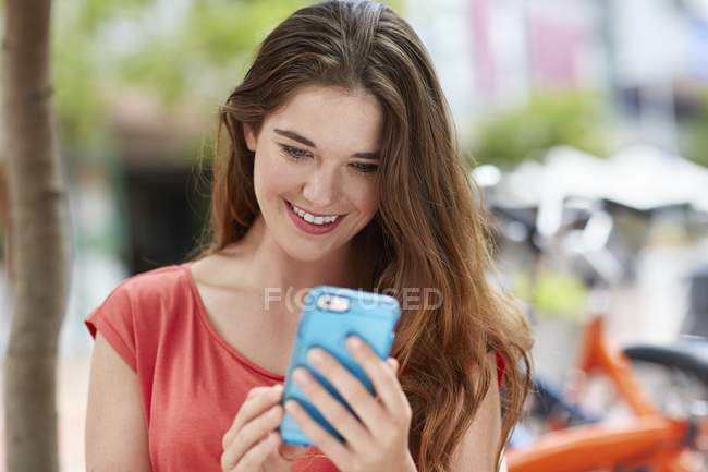 Woman holding smartphone and looking down. — Stock Photo
