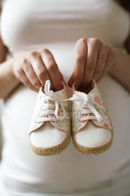 Mulher grávida segurando sapatos de bebê. — Fotografia de Stock