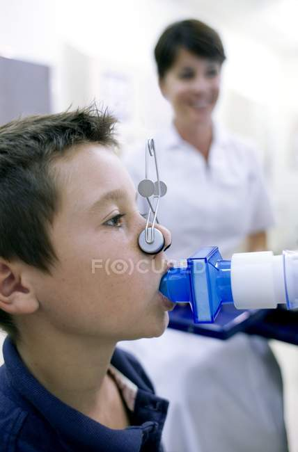 Preteen boy undergoing lung function test with female nurse. — Stock Photo