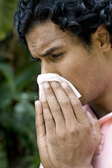 Man sneezing into handkerchief outdoors. — Stock Photo