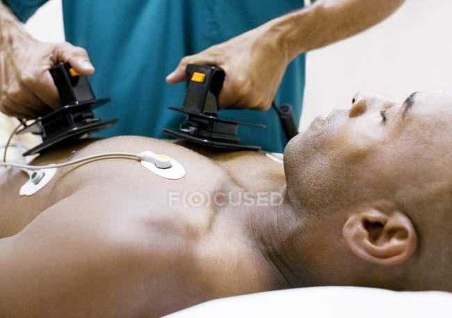 Доктор керуючої надзвичайних defibrillation до пацієнта. — стокове фото