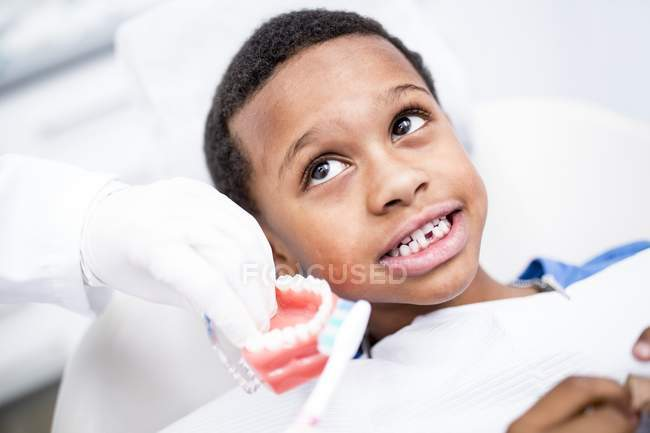 Close-up of dentist hands showing boy how brushing teeth. — Stock Photo