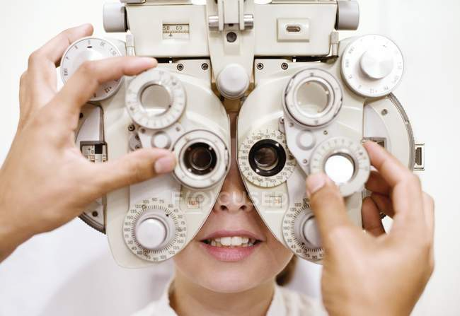 Optician using phoropter for eye examination preteen girl. — Stock Photo