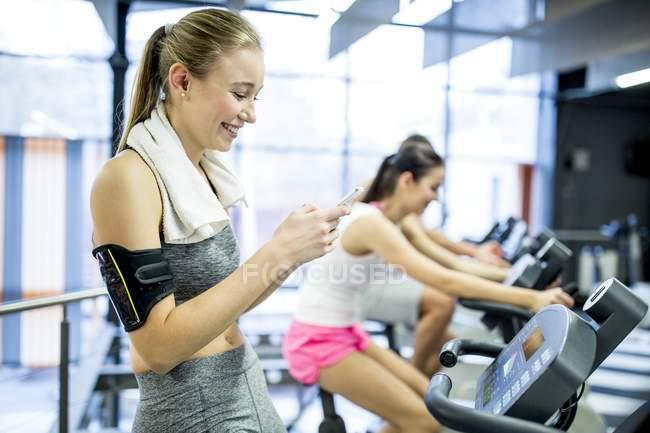 Frau mit Smartphone während des Trainings im Fitnessstudio — Stockfoto