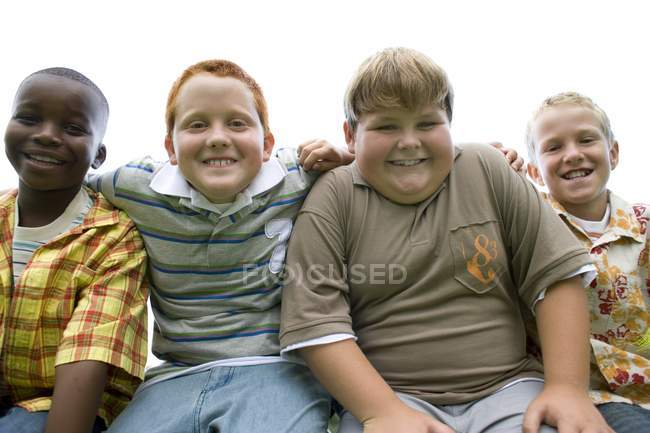 Ritratto di gruppo di ragazzi in età elementare seduti all'aperto . — Foto stock